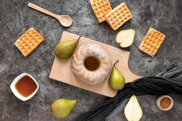 Mise à plat de beignets sur une planche à découper avec des poires et des gaufres