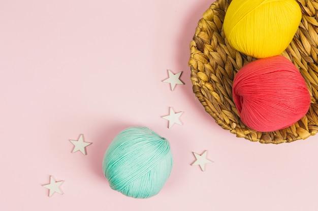 Mise à plat de belles boules de coton vert menthe, rose corail et jaune foncé dans un panier avec des étoiles en bois blanc autour et un fond rose pastel