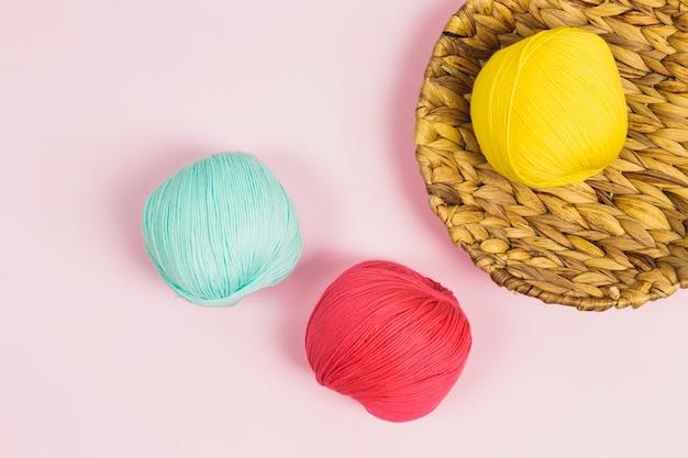 Mise à plat de belles boules de coton vert menthe, rose corail et jaune foncé dans un panier avec fond rose pastel