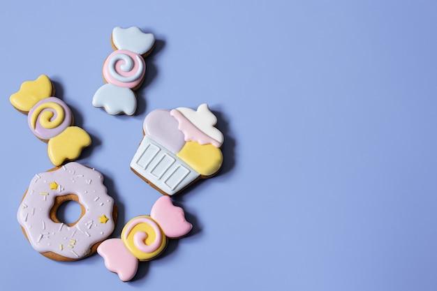 Mise à plat de biscuits de pain d'épice glacés brillants sur un espace de copie de fond bleu.