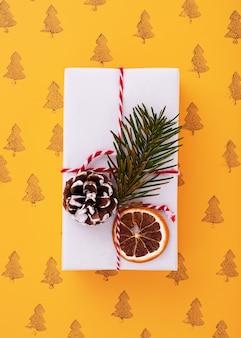 Mise à plat d'une boîte cadeau décorée blanche, motif d'arbres de noël dans le fond orange