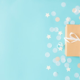 Mise à plat avec une boîte-cadeau en papier artisanal isolée attachée avec des confettis en papier ruban, étoile et cercle ou des paillettes sur une surface pastel bleue