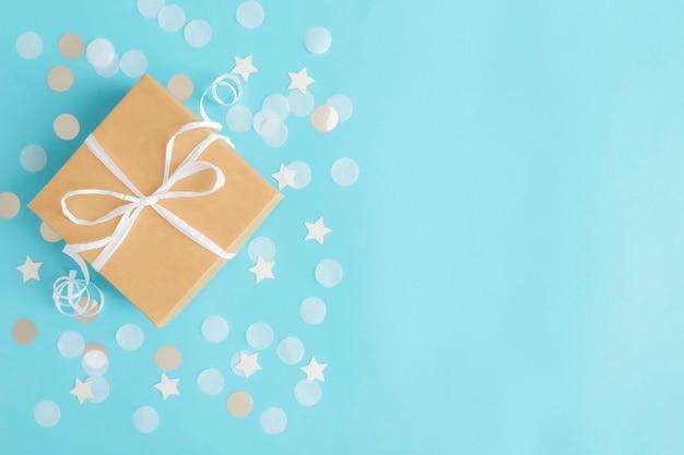 Mise à plat avec boîte-cadeau de papier kraft isolé attaché avec des confettis de papier ruban, étoile et cercle ou des paillettes sur fond pastel bleu.