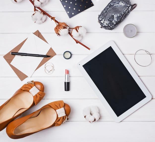 Mise à plat avec branche de coton, chaussures et tablette