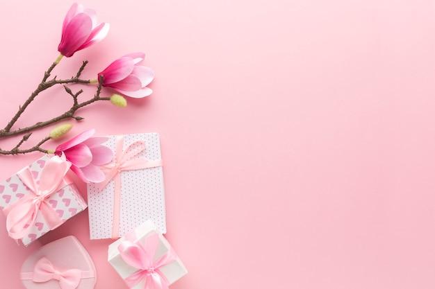 Mise à plat de cadeaux roses avec magnolia et espace copie