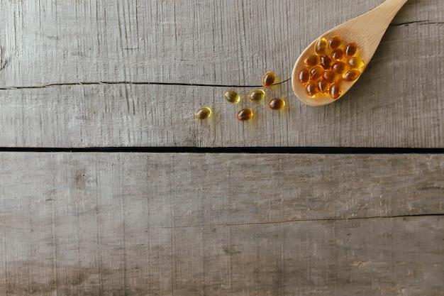 Mise à plat avec des capsules d'oméga 3 sur une cuillère sur le fond en bois. concept de santé. pilules de vitamines.