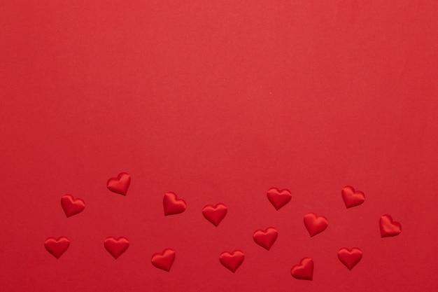 Mise à plat carte de voeux avec de nombreuses formes de coeur rouge sur fond rouge avec fond