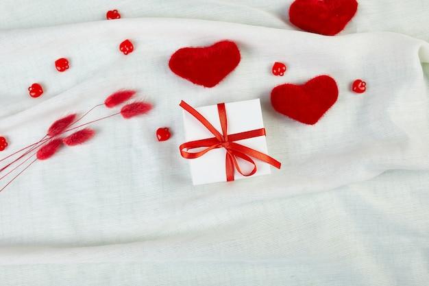 Mise à plat de la carte de voeux saint valentin avec boîte-cadeau et coeurs sur la texture de tissu blanc