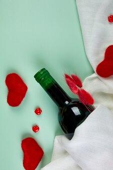 Mise à plat de la carte de voeux saint valentin avec bouteille de vin rouge et coeurs sur bleu