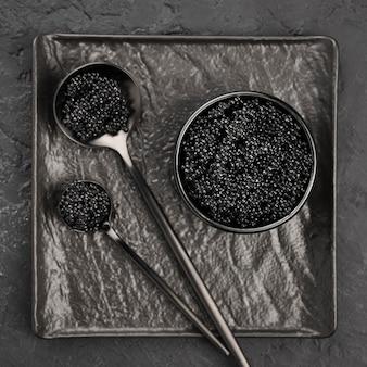 Mise à plat de caviar noir dans un bol et des cuillères