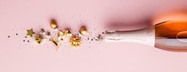 Mise à plat de la célébration. bouteille de champagne et décoration dorée sur rose