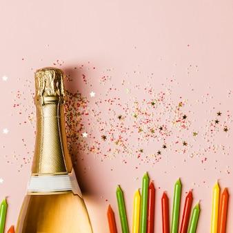 Mise à plat de la célébration. bouteille de champagne avec paillettes sur fond rose.