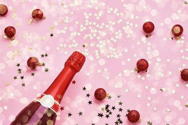 Mise à plat de la célébration de noël. bouteille de champagne avec décoration de noël rouge sur fond rose. vue de dessus, copiez l'espace.