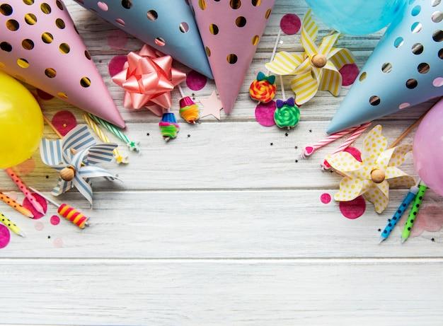 Mise à plat avec des chapeaux d'anniversaire, des confettis et des rubans sur bois blanc