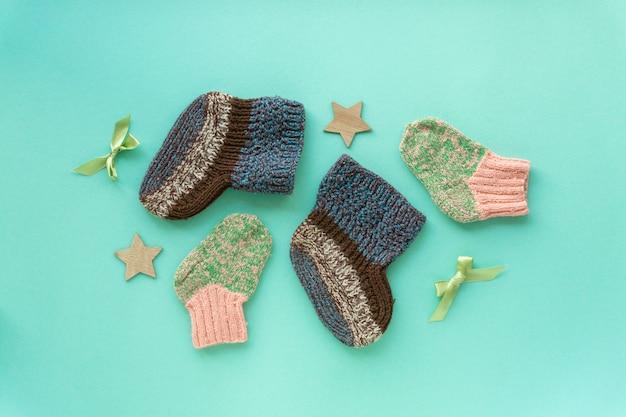 Mise à plat de chaussettes tricotées bébé pour garçon et fille sur fond de menthe, vue de dessus.