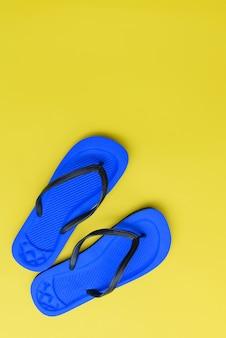 Mise à plat, chaussures de tongs de plage sur fond jaune, vue de dessus