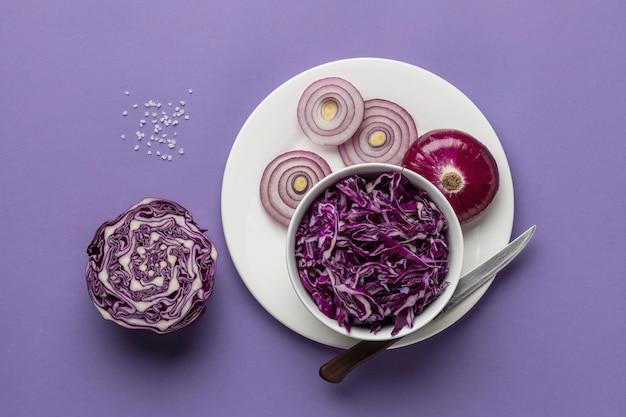 Mise à plat de chou dans un bol avec l'oignon sur une assiette et un couteau