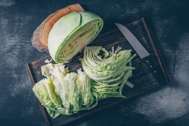 Mise à plat de chou tranché et haché dans une planche à découper et un couteau avec un morceau de bois sur fond texturé sombre. horizontal