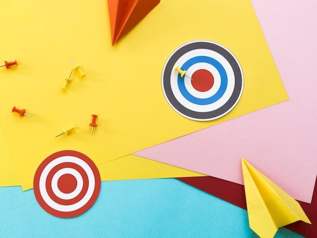 Mise à plat de cibles en papier avec des épingles et des avions en papier