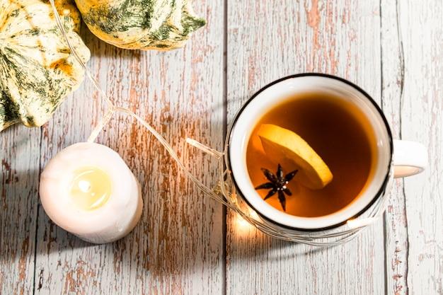 Mise à plat de citrouilles, feuilles d'automne sèches, bougies sur table en bois