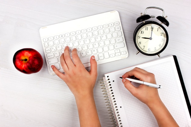 Mise à plat avec clavier blanc, pomme, réveil et mains
