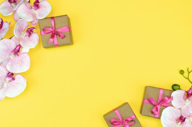 Mise à plat des coffrets cadeaux avec ruban rose sur fond jaune avec fleur d'orchidée.