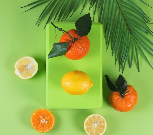 Mise à plat colorée lumineuse de mandarines, citrons et feuilles tropicales
