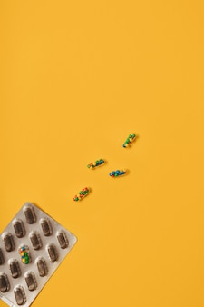 Mise à plat colorée et vibrante de capsules de pilules médicinales remplies de sucre candi saupoudre sur fond jaune. concept créatif d'utilisation de médicaments surdosés et de dépendance aux compléments alimentaires.