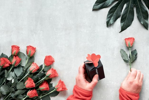 Mise à plat, composition avec bouquet de fleurs roses et feuilles de plantes exotiques. mains tenant rose et coffret cadeau avec coeurs. vue de dessus sur fond de pierre clair. valentin, anniversaire ou concept de fête des mères.