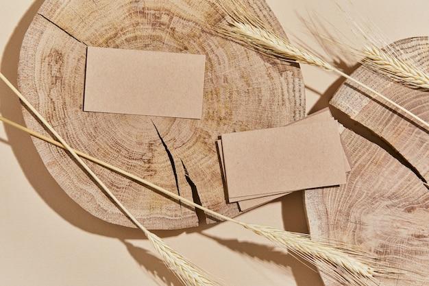 Mise à plat de composition créative avec maquettes de cartes de visite, bois, matériaux naturels, plantes sèches et accessoires personnels. couleurs neutres, vue de dessus, modèle.