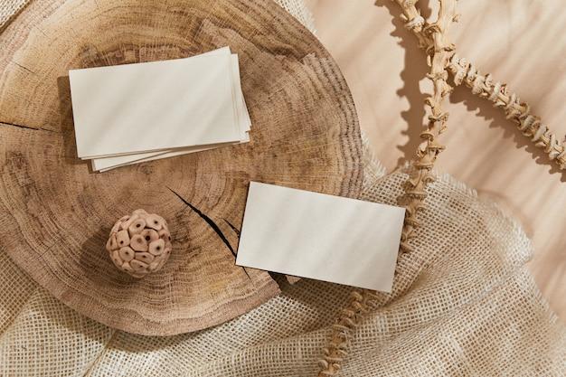 Mise à plat de composition créative avec maquettes de cartes de visite, textile, bois, matériaux naturels, plantes sèches et accessoires personnels. couleurs neutres, vue de dessus, modèle.