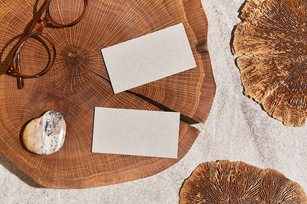 Mise à plat de composition élégante avec maquettes de cartes de visite, roche, bois, matériaux naturels, plantes sèches et accessoires personnels. couleurs neutres, vue de dessus, modèle.