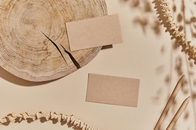 Mise à plat de la composition intérieure avec maquettes de cartes de visite, textile, roches, bois, matériaux naturels, plantes sèches et accessoires personnels. couleurs neutres, vue de dessus, modèle.