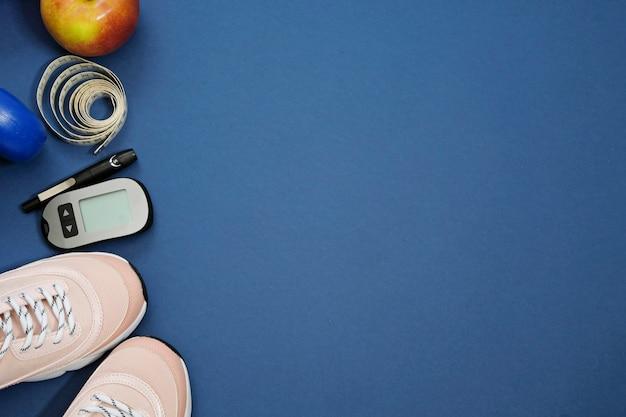 Mise à plat avec le concept de perte de poids de diabète de régime. sneakers, ruban à mesurer, glucomètre sur fond bleu