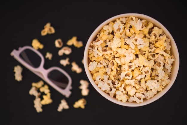 Mise à plat. copyspace. concept de cinéma. contexte. pop-corn, tasse et lunettes 3d sur fond noir.