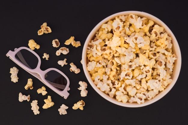 Mise à plat. copyspace. concept de cinéma. contexte. pop-corn, tasse et lunettes 3d sur fond sombre. zoom sur les lunettes 3d