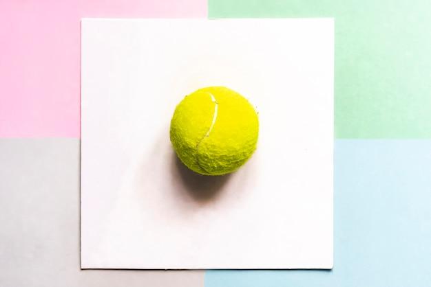 Mise à plat créative avec bal de tennis isolé dans un cadre blanc sur fond de couleur, concept d'idée créative f
