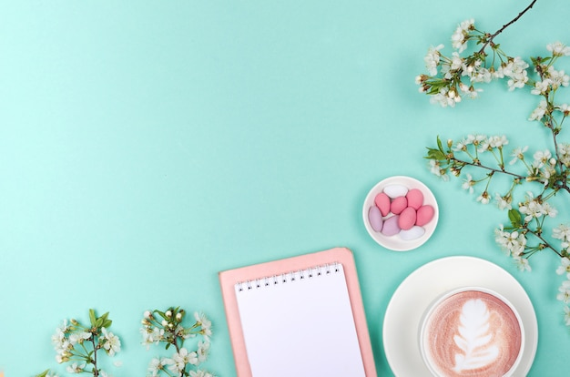 Mise à plat créative de bureau, bloc-notes et objets de style de vie sur fond vert