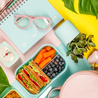 Mise à plat créative avec déjeuner sain et fournitures de bureau