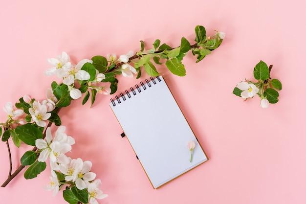 Mise à plat créative du cadre du bloc-notes en spirale vierge et des pétales de fleurs de pommier sur fond rose pastel avec espace de copie dans un style minimal, modèle pour le lettrage, le texte ou votre conception.