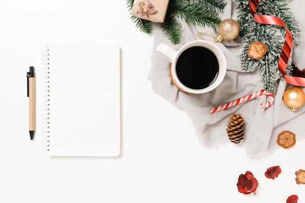 Mise à plat créative minimale de la composition traditionnelle de noël d'hiver et du nouvel an. vue de dessus ouvrir le cahier noir de maquette pour le texte sur l'espace de copie de fond blanc.