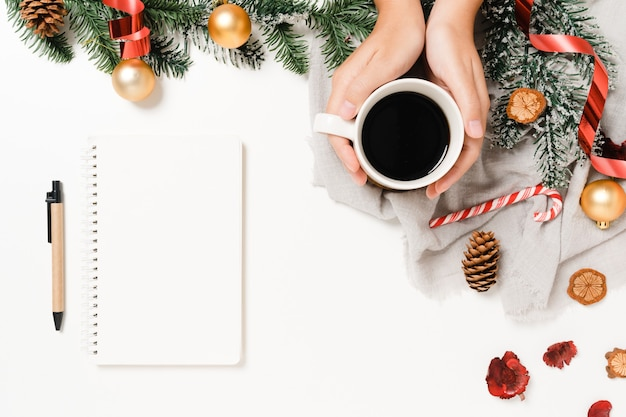 Mise à plat créative minimale de la composition traditionnelle de noël d'hiver et du nouvel an. vue de dessus ouvrir le cahier noir de maquette pour le texte sur fond blanc.