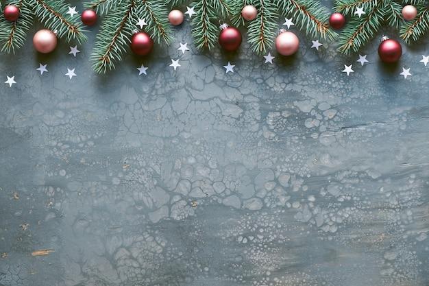 Mise à plat créative de noël avec copie-espace sur tableau d'art fluide acrylique gris. bordure décorative avec des brindilles de sapin et de houx décorées de boules de verre rouge foncé et d'étoiles en bois.