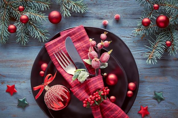 Mise à plat avec des décorations de noël en vert et rouge avec des baies givrées, des bibelots, des assiettes et de la vaisselle