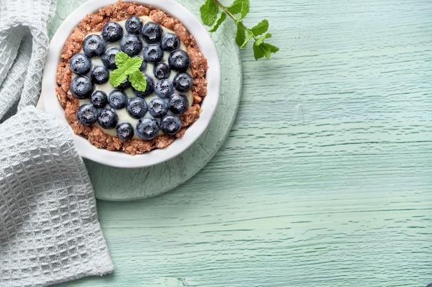 Mise à plat de délicieuses tartelettes aux bleuets avec crème pâtissière à la vanille et feuille de menthe