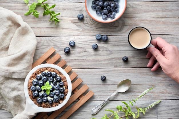 Mise à plat de délicieuses tartelettes aux bleuets avec crème à la vanille et main avec café
