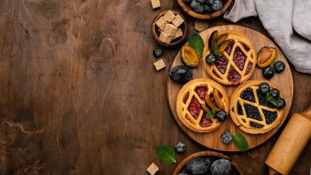 Mise à plat de délicieuses tartes aux fruits avec prunes et espace copie