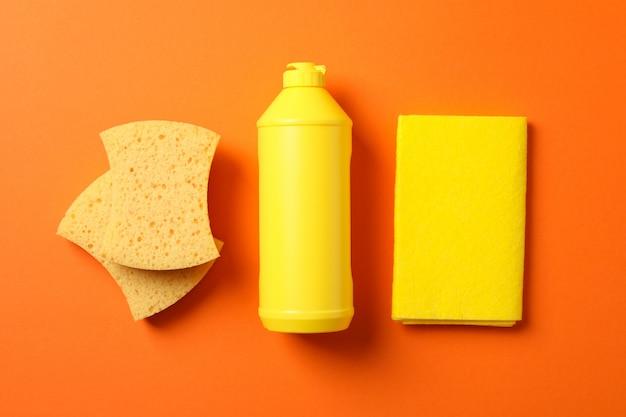 Mise à plat avec détergent et produits de nettoyage sur orange, vue de dessus