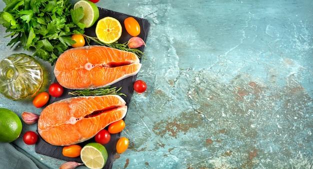 Mise à plat de deux steaks de saumon crus avec des ingrédients de cuisson sur un mur cyan bleu clair.