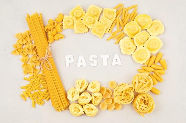 Mise à plat avec différents types de pâtes italiennes traditionnelles. penne, tagliatelle, fusilli, farfalle, spaghetti et autres. concept de cuisine italienne traditionnelle. vue de dessus